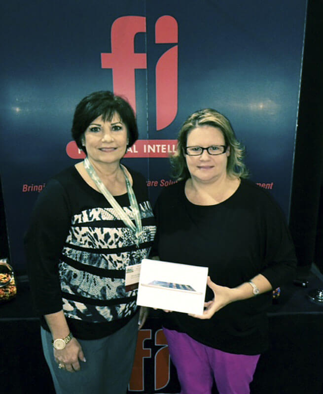 At the Arkansas Association of Counties Conference in Little Rock, Financial Intelligence (FI) gave away an Apple IPad Mini. Here, Mandy Epperson with Financial Intelligence is presenting Michelle Frost, County Clerk of Johnson County, with her prize.  Thanks to everyone for participating.